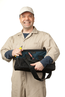 Worker in coveralls and cap, with toolkit and tools
